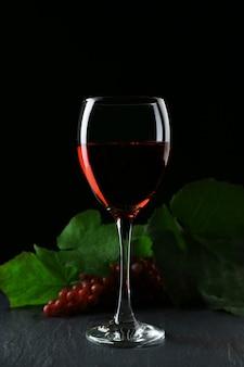 Uma taça de vinho e uvas vermelhas, em fundo cinza-escuro