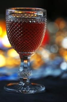 Uma taça de vinho rosa em um fundo iluminado desfocado