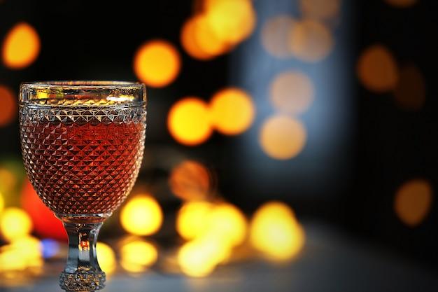 Uma taça de vinho rosa em uma superfície iluminada e embaçada