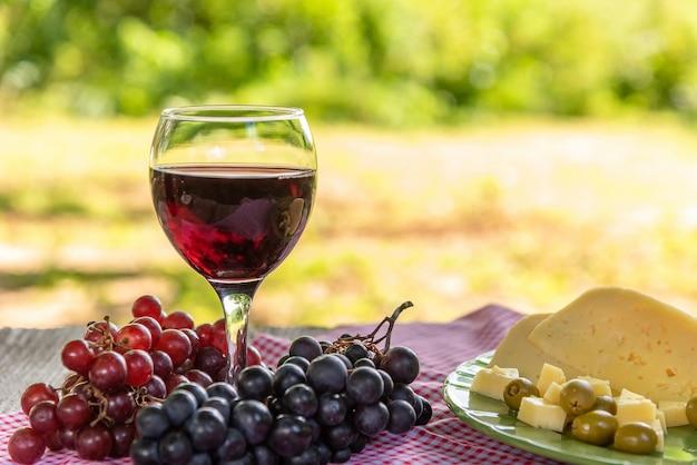 Uma taça de vinho tinto e um prato de queijo, azeitonas e uvas na mesa.