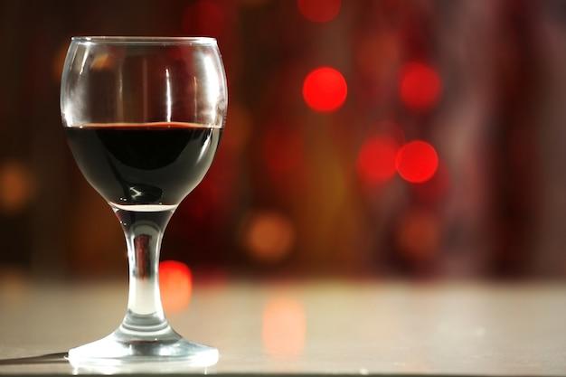 Uma taça de vinho tinto em um fundo iluminado e desfocado
