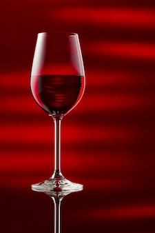 Uma taça de vinho tinto em uma mesa lustrosa.
