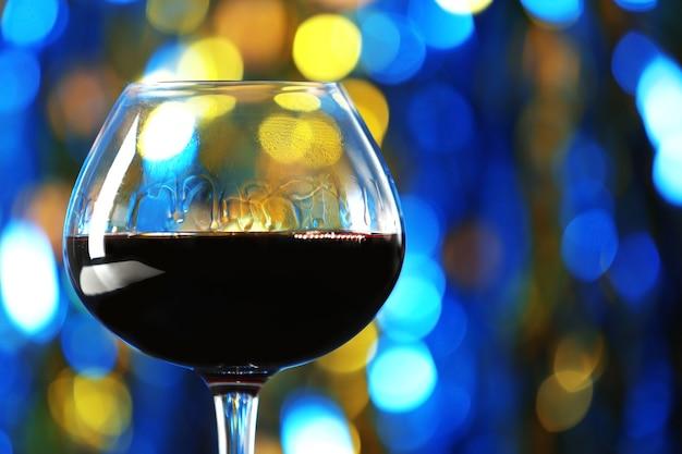 Uma taça de vinho tinto em uma superfície iluminada e embaçada