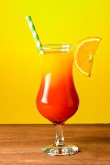 Uma taças de vidro com coquetel do nascer do sol em uma mesa de madeira com fundo amarelo.