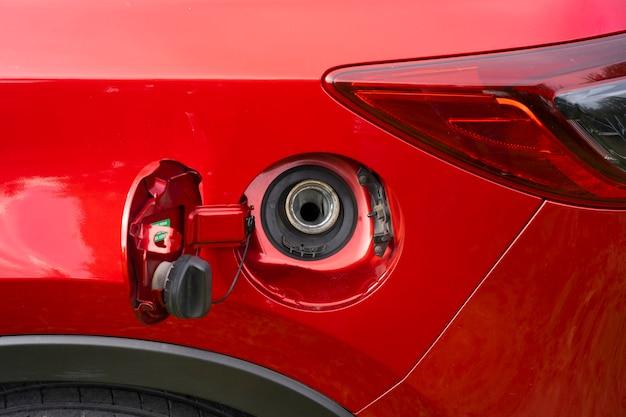 Uma tampa do tanque de combustível aberta de um carro vermelho para abastecer com gasolina ou óleo diesel no tanque de gasolina.