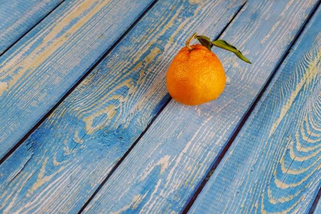 Uma tangerina com folhas na mesa de madeira
