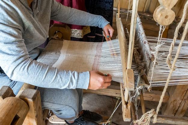 Uma tecelã faz um tecido em um velho tear artesanal.