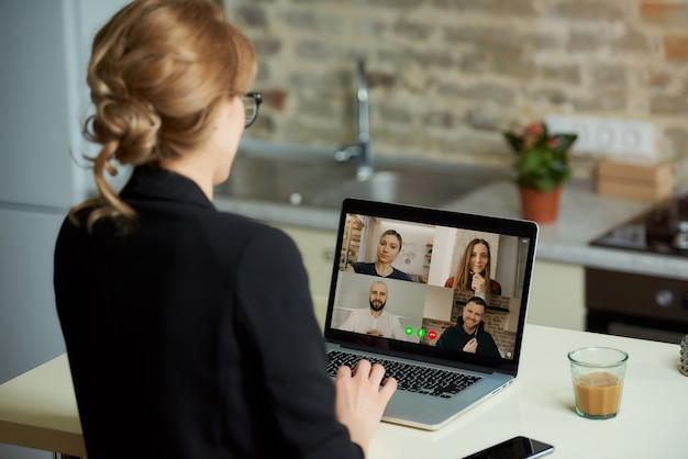 Uma tela do laptop por cima do ombro de uma mulher.