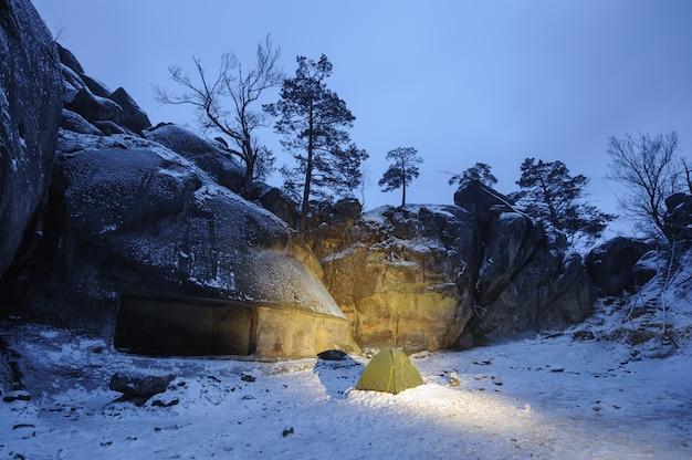 Uma tenda verde que está na neve ao lado do penhasco rochoso