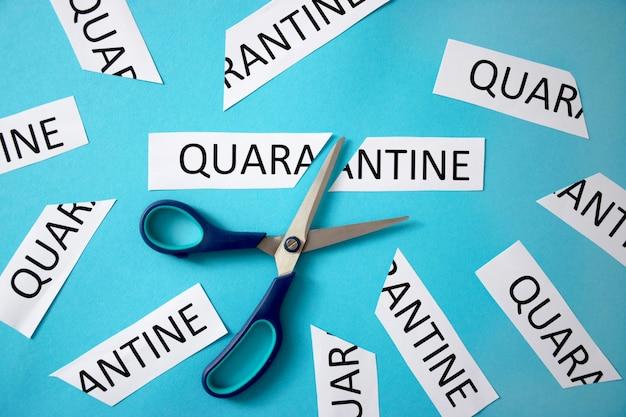 Uma tesoura está cortando um pedaço de papel com a palavra quarentena. o isolamento acabou. de volta ao trabalho. restrições de quarentena relaxantes. fim da quarentena do coronavirus.