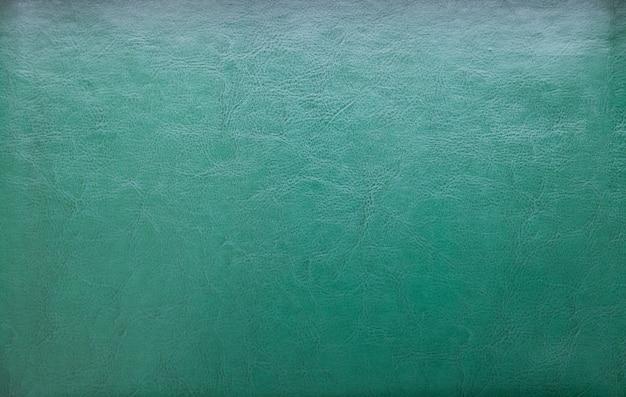 Uma textura de couro verde natural. fundo com efeito de marcações de linhas de couro
