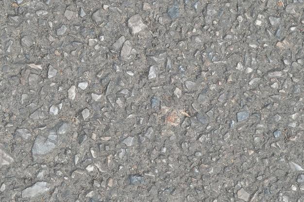 Uma textura de pavimento de asfalto cinzento escuro e suave com pequenas rochas
