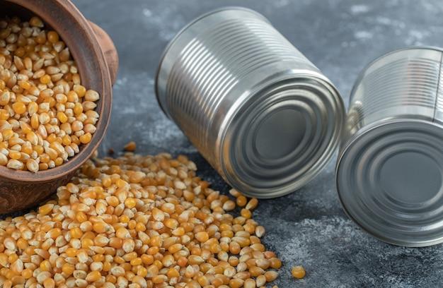 Uma tigela antiga cheia de sementes de pipoca crus com latas de metal.