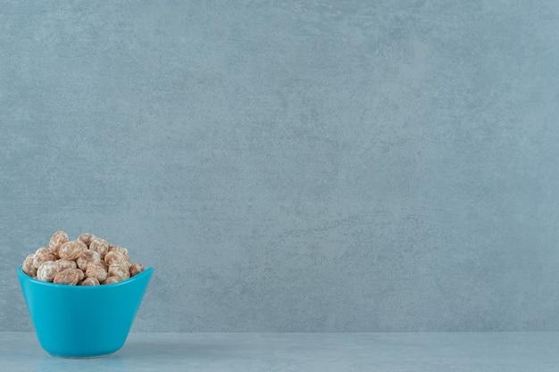 Uma tigela azul cheia de um delicioso pão de mel doce na superfície branca