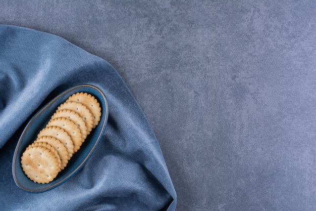 Uma tigela azul de biscoitos de manteiga para chá na toalha de mesa.