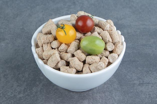 Uma tigela branca cheia de cereais crocantes de centeio e tomates coloridos.
