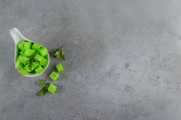 Uma tigela branca cheia de doces verdes doces com folhas de hortelã em uma mesa de pedra.