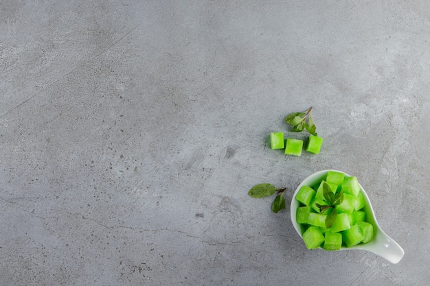 Uma tigela branca cheia de doces verdes doces com folhas de hortelã em uma superfície de pedra
