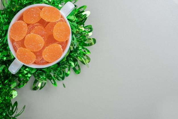 Uma tigela branca cheia de geleias de laranja açucaradas.