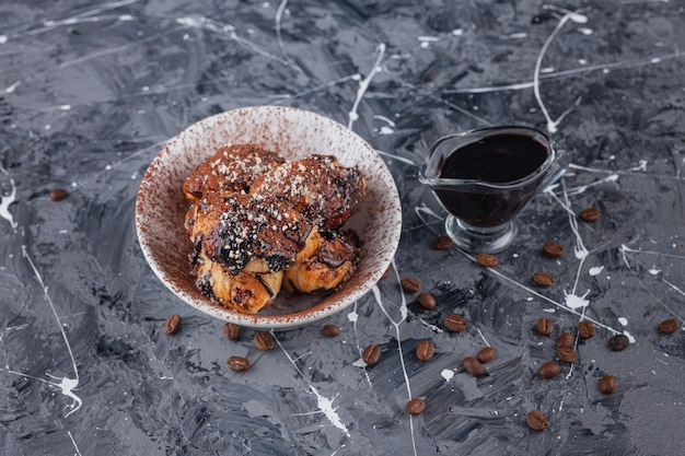 Uma tigela branca cheia de mini croissants com grãos de café aromáticos.