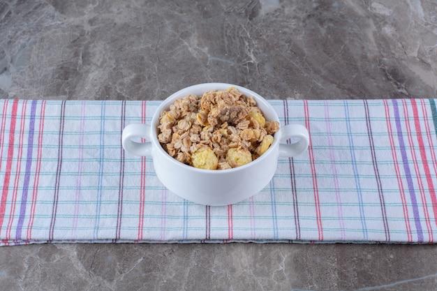 Uma tigela branca cheia de saborosos flocos de milho saudáveis na toalha de mesa.