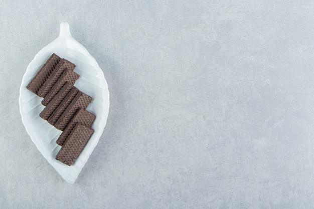 Uma tigela branca cheia de waffles de chocolate.
