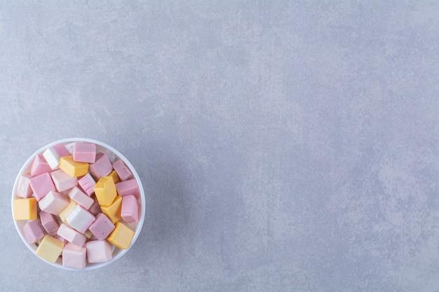 Uma tigela branca com confeitaria doce rosa e amarela pastila. foto de alta qualidade