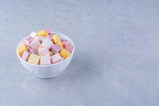 Uma tigela branca com confeitaria rosa e amarela pastila