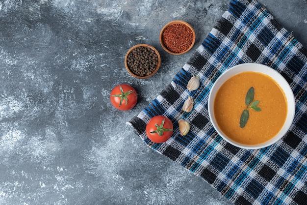 Uma tigela branca de sopa de lentilha com legumes em uma bela toalha de mesa.