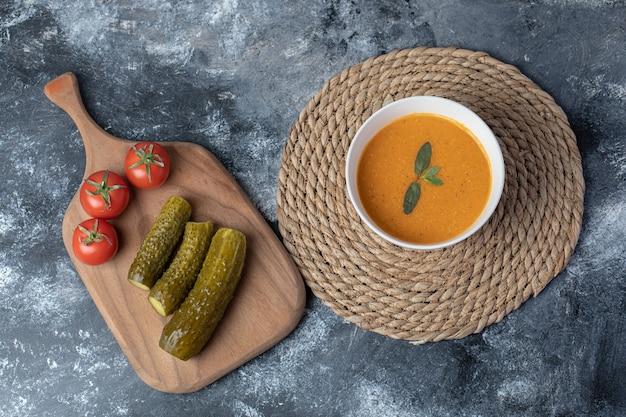 Uma tigela branca de sopa de lentilha com legumes.