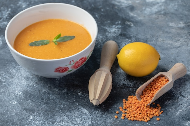 Uma tigela branca de sopa de lentilha com um alargador de madeira.