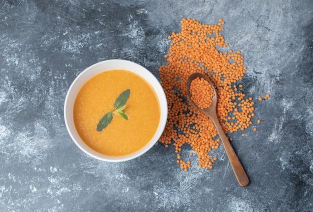 Uma tigela branca de sopa de lentilha com uma colher de pau.