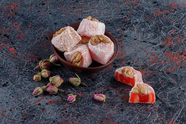 Uma tigela cheia de delícias tradicionais turcas com flores rosas