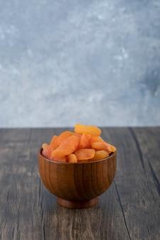 Uma tigela cheia de frutas de damasco secas saudáveis em uma mesa de madeira.