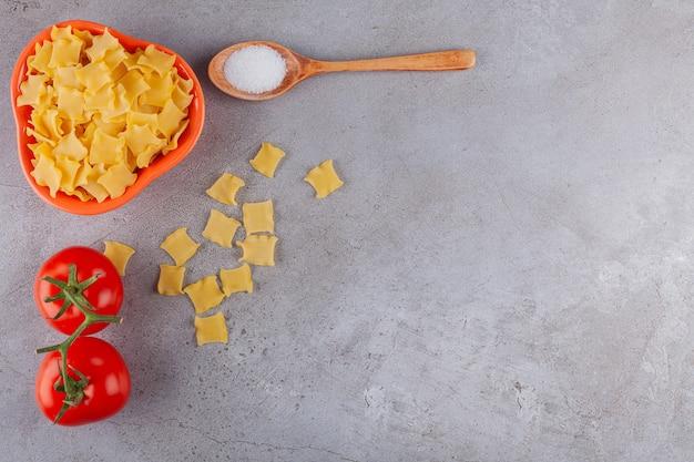 Uma tigela cheia de macarrão ravioli cru com tomates vermelhos frescos e sal.