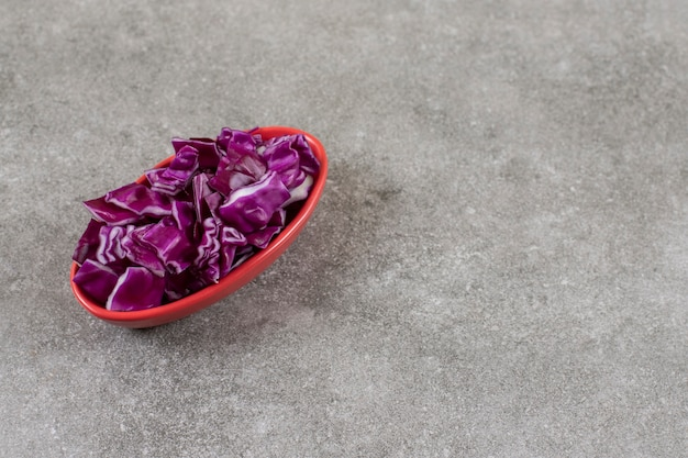 Uma tigela cheia de pilha de repolho roxo cortado em uma mesa de pedra.