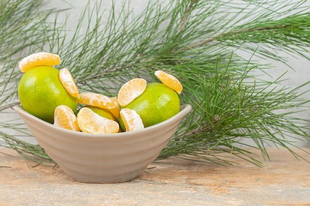 Uma tigela cheia de suculentas tangerinas verdes em uma pedra.