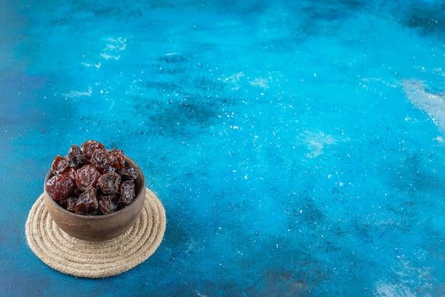 Uma tigela de ameixas secas em um tripé na superfície azul