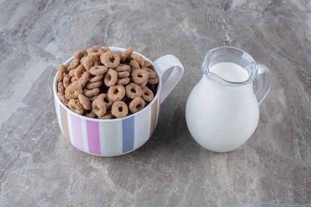 Uma tigela de anéis de cereais de chocolate saudáveis com uma jarra de vidro de leite.