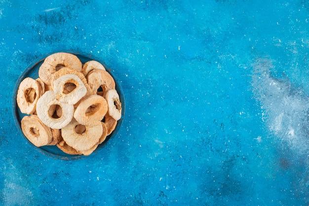 Uma tigela de anéis de maçã seca, na mesa azul.