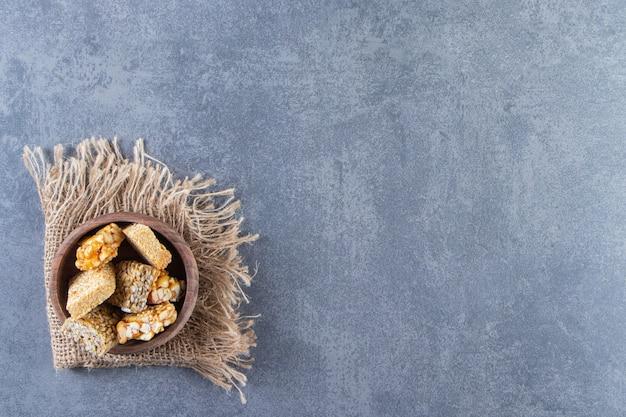 Uma tigela de barras de granola em uma textura, no fundo de mármore.