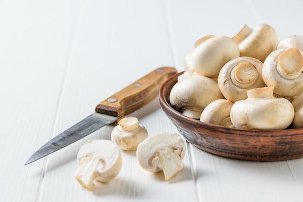 Uma tigela de barro com cogumelos, uma faca e pedaços de cogumelos em uma mesa de madeira branca