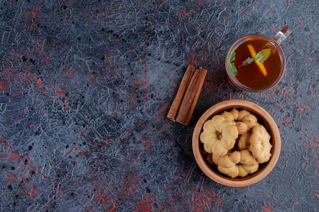 Uma tigela de barro com cupcakes redondos com um buraco e uma xícara de chá quente