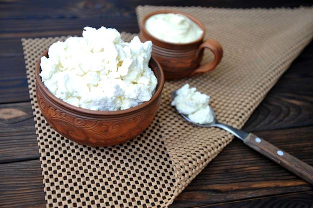 Uma tigela de barro com queijo cottage uma caneca de barro com creme de leite e uma colher em uma mesa de madeira