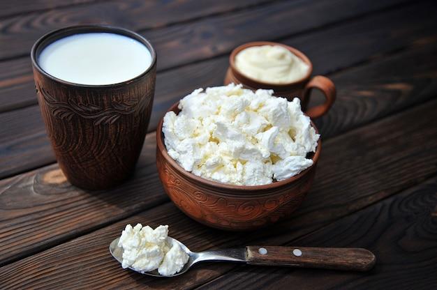 Uma tigela de barro com queijo cottage uma caneca de barro com creme de leite uma caneca com leite e uma colher sobre uma mesa de madeira
