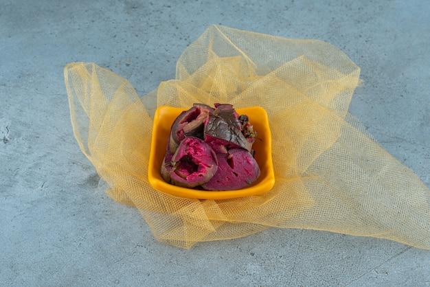 Uma tigela de berinjela fermentada em tule, na mesa azul.