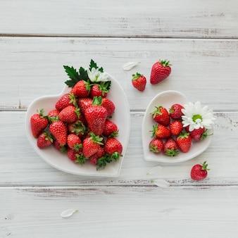 Uma tigela de cerâmica de forma de coração de morangos vermelhos suculentos na mesa de madeira branca. conceito de lanches saudáveis e dieta.