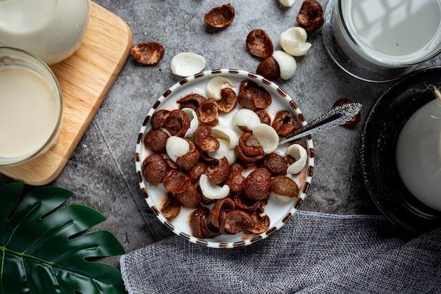 Uma tigela de cereal com sabor de chocolate misturado com leite no café da manhã.