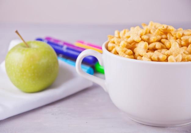 Uma tigela de cereal em forma de estrela seca e uma garrafa de leite