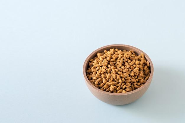 Uma tigela de comida animal em um fundo azul. fechar-se